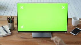 Mão do ` s da mulher usando o PC com o monitor verde do tela táctil video estoque