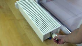 Mão do ` s da pessoa que ajusta a temperatura do termostato do radiador vídeos de arquivo