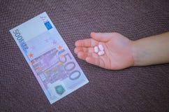Mão do ` s das crianças com os comprimidos na frente de cinco cem proibições do Euro Imagem de Stock