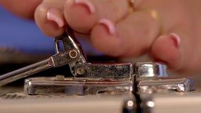 A mão do ` s das mulheres abre a trava de uma grande mala de viagem do cromo video estoque