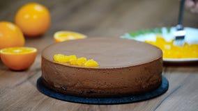 A mão do ` s das mulheres decorou o bolo da musse de chocolate com segmentos alaranjados filme