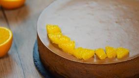 A mão do ` s das mulheres decorou o bolo da musse de chocolate com segmentos alaranjados video estoque