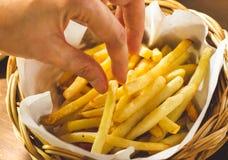 A mão do ` s das mulheres está pegarando batatas fritas Imagem de Stock