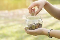 A mão do ` s das mulheres pôs moedas do dinheiro na garrafa de vidro para o conceito das economias e da doação Fotos de Stock Royalty Free