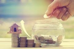 A mão do ` s das mulheres pôs moedas do dinheiro na garrafa de vidro para o conceito das economias e da doação para a casa de com Imagem de Stock