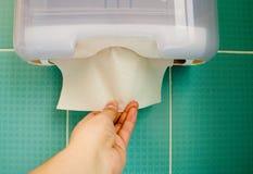 A mão do ` s das mulheres retira um guardanapo de papel da bandeja imagens de stock royalty free