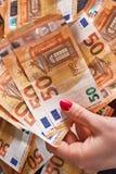 Mão 50 do ` s de Woomen cinqüênta cédulas das contas dos euro no fundo do dinheiro Fotos de Stock