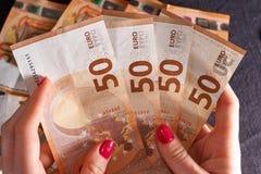 Mão 50 do ` s de Woomen cinqüênta cédulas das contas dos euro no fundo do dinheiro Imagens de Stock Royalty Free