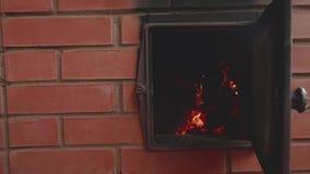 A mão do ` s do homem abre os dedos ardentes da porta da chaminé pouco Vista da chama na fornalha aberta Movimento lento filme