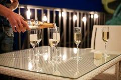 A mão do ` s do homem derrama o champanhe em uns copos de vinho imagens de stock royalty free