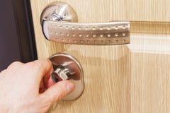 A mão do ` s do homem fecha o fechamento na porta Gire a trava de porta imagens de stock royalty free