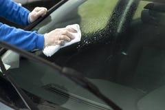 A mão do ` s do homem limpa o vidro do ` s do carro com um pano Fotografia de Stock