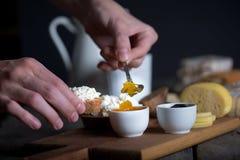 Mão do ` s do homem que põe o doce da bacia sobre o pão com queijo da ricota Fotos de Stock