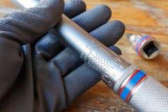 A mão do ` s do mecânico na luva de trabalho guarda a chave de torque Fotos de Stock