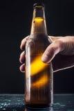 Mão do ` s dos homens que guarda uma garrafa da cerveja foto de stock royalty free
