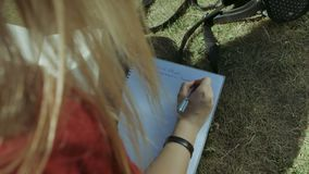 Mão do ` s do estudante fêmea com escrita da pena no caderno video estoque