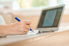 Mão do ` s do estudante que mantém uma pena e que escreve no caderno Imagens de Stock