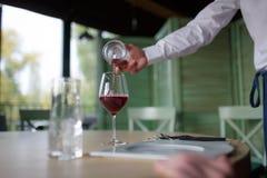 A mão do ` s do garçom derrama o vinho tinto no vidro fotografia de stock royalty free