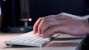 Mão do ` s do homem com fim esperto do relógio acima do tipo no teclado do desktop no espaço de trabalho O homem de negócios novo filme