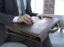 Mão do ` s do homem de negócios com suitecase em um escritório moderno Imagem de Stock