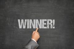 Mão do ` s do homem de negócios que aponta no texto do vencedor escrito no quadro-negro Fotografia de Stock