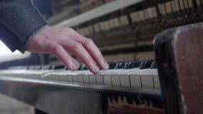 A mão do ` s do homem está pressionando chaves do piano de madeira clássico velho, empoeirado e abandonado video estoque