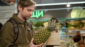A mão do ` s do homem toma um abacaxi fresco da prateleira do alimento Produtos orgânicos Vegetais e frutas Alimento saudável Com filme