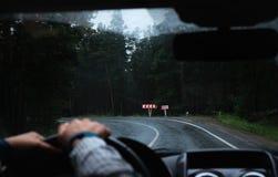 Mão do ` s do motorista em um volante dentro de um carro em uma estrada Fotografia de Stock Royalty Free