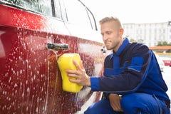 Mão do ` s do trabalhador que lava o carro vermelho com esponja amarela foto de stock