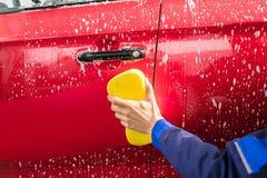 Mão do ` s do trabalhador que lava o carro vermelho com esponja amarela fotografia de stock
