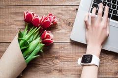 Mão do smartwatch vestindo da mulher no laptop Vista superior Fotos de Stock Royalty Free