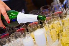 A mão do Sommelier derrama o vinho espumante branco em copos de vinho em uma restauração do partido do verão do ar livre imagem de stock royalty free