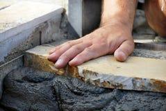 Mão do trabalhador no flagstone fotografia de stock royalty free