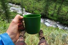 Mão do turista que guarda a caneca plástica Imagem de acampamento Apreciando a vida do nômadas do resto e do rio e da floresta da fotos de stock