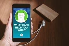 Mão do usuário que guarda a conversa móvel com bot do bate-papo na tela do telefone imagens de stock royalty free