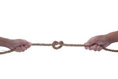 Mão dois que puxa uma corda com forma do coração Fotografia de Stock