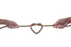 Mão dois que puxa uma corda com forma do coração Foto de Stock