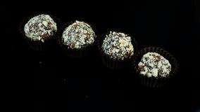 A mão dos confeitos do close up pôs seis doces de chocolate sobre o fundo preto video estoque