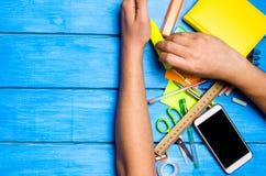 a mão dos estudantes da escola limpa afastado as fontes de escola no fundo de madeira azul da tabela o estudante prefere executar fotografia de stock royalty free
