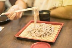 A mão dos hashis do uso da mulher para apertar um macarronete em um prato de bambu, macarronete japonês, it's chama Soba, foco  Imagem de Stock Royalty Free