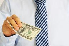 A mão dos homens que guarda notas de dólar do americano cem do dinheiro Mão do dinheiro de oferecimento do homem de negócios Fotografia de Stock Royalty Free