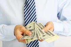 A mão dos homens que guarda notas de dólar do americano cem do dinheiro Mão do dinheiro de oferecimento do homem de negócios Home Imagens de Stock Royalty Free