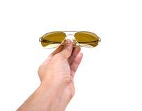 A mão dos homens que mantém mais glassest do sol isolado nos wi brancos do fundo Imagem de Stock