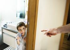A mão dos pais pede o menino escovar seus dentes imagem de stock royalty free