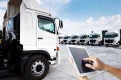 A mão dos povos está usando a tabuleta que a foto múltipla com a frota de caminhão nova está estacionando na jarda para a tecnolo fotos de stock royalty free