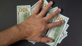 A mão dos povos toma o close up do dinheiro O braço agarra dólares contra um contexto preto filme