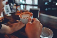 Mão e café que tomam a distância Café quente da bebida na manhã imagens de stock royalty free