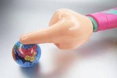 Mão e globo plásticos imagem de stock