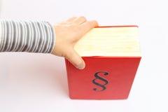Mão e livro vermelho Imagem de Stock