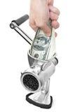 Mão e moedor com dólares imagem de stock